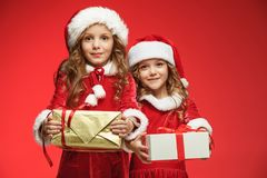 Two happy girls in santa claus hats with gift boxes at studio Royalty Free Stock Photo