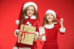 Two happy girls in santa claus hats with gift boxes Stock Photography