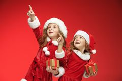 Two happy girls in santa claus hats with gift boxes Stock Photo