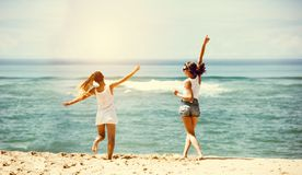 Two happy girls sea beach fun. Two happy girls friends are having fun at sea beach. Jumping and dancing Royalty Free Stock Photo