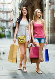 Two happy girls with shopping bags walking. On city street. Focus on brunette Stock Images