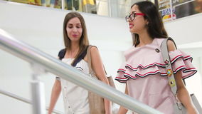 Two happy girls on shopping. Two happy girls in shopping center. Young attractive women going up strairs in mall stock footage