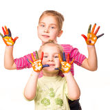 Two happy girls showing hands painted in bright colors Royalty Free Stock Image