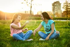 Two happy girls sit on the grass stock images