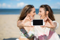 Two happy girls sitting on beach taking selfie laughing Royalty Free Stock Photos