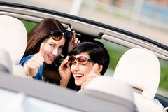 Two happy girls sitting in the car and thumbing up Royalty Free Stock Photography