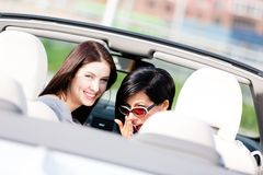 Two happy girls sitting in the car turn back Stock Images