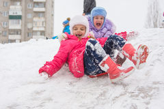Two happy girls slide down the icy hill Stock Photos