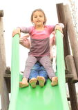 Two happy girls on a slide Stock Images
