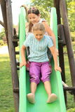 Two happy girls on a slide Royalty Free Stock Image