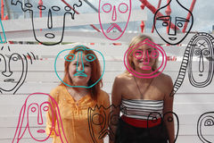Two happy girls smile behind glass wall with faces royalty free stock photo