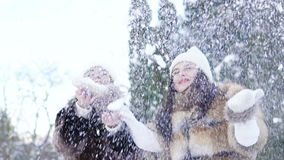 Two happy girls smiling and throwing up snow in the park. Slowly.  stock footage