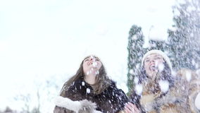 Two happy girls smiling and throwing up snow in the park. Slowly.  stock video footage