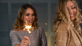 Two happy girls with a sparkler in their hands. SLOW MOTION: two happy girls with a sparkler in their hands stock video footage