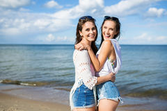 Two happy girls standing together on beach hugging stock photo