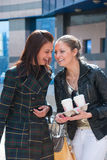 Two happy girls on a street with coffee stock photography