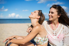 Two happy girls sunbathing on beach laughing. Side portrait of two happy girls sunbathing on beach laughing Royalty Free Stock Images