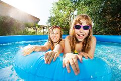 Two happy girls swimming in the pool at sunny day. Portrait of two happy girls swimming in the inflatable pool with blue rubber ring at sunny day stock images