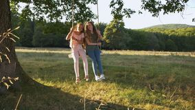 Two happy girls swinging outdoors - camera in low angle rising stock video footage