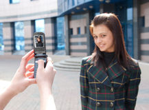 Two happy girls take pictures on a street. Girl take a picture of an other girl on a street by mobile phone. Focus to mobile phone Stock Photo