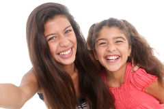 Two happy girls. Taking a self portrait on white background Stock Images