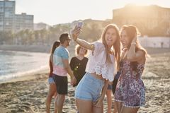 Two happy girls taking selfie on beach making faces. Portrait of two happy girls taking selfie on beach making faces Royalty Free Stock Photography