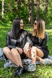 Two happy girls talking and laughing in nature and sitting on the blanket in meadow on a sunny spring day. Forest in background. Girls wear a black dress and royalty free stock photo