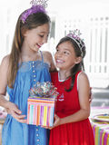 Two Happy Girls In Tiaras Holding Present. Portrait of two happy girls in tiaras holding present Royalty Free Stock Image