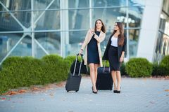 Two happy girls traveling abroad together, carrying suitcase luggage in airport.  royalty free stock photo