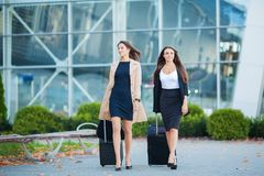 Two happy girls traveling abroad together, carrying suitcase luggage in airport.  stock images