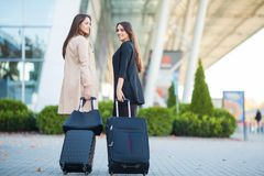 Two happy girls traveling abroad together, carrying suitcase luggage in airport.  stock photo