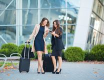 Two happy girls traveling abroad together, carrying suitcase luggage in airport.  stock image
