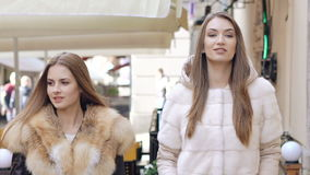 Two happy girls walking in furry coats in shopping center. Slowly.  stock video