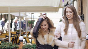 Two happy girls walking in furry coats in shopping center. Slowly.  stock footage