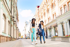 Two happy girls walking holding hands Stock Photo