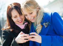 Two happy girls. Watching something in mobile phone Royalty Free Stock Images