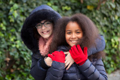Two happy girls at winter with coats Royalty Free Stock Images