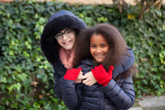 Two happy girls at winter with coats Royalty Free Stock Photography