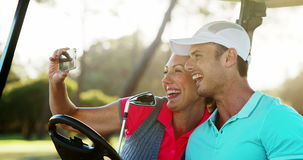 Two happy golfers taking a selfie in golf buggy. At golf course 4k stock footage