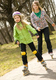Two happy grils on roller-skates. Two happy grils ride on roller-skates Royalty Free Stock Photo