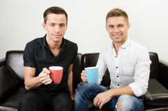 Two happy guys are drinking coffee. Two attractive guys in the studio. Business and education. Technology and sport stock photography