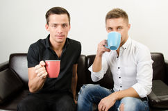 Two happy guys are drinking coffee. Two attractive guys in the studio. Business and education. Technology and sport stock photos