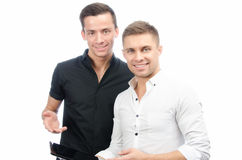 Two happy guys and a tablet. Work and study. White background. Two attractive guys in the studio. Business and education. Technology royalty free stock image