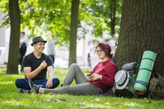 Two happy hikers laugh sitting on the grass. Telephoto shot Stock Images