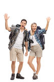 Two happy hikers waving at camera. Full length portrait of two happy hikers waving at the camera isolated on white background Royalty Free Stock Image