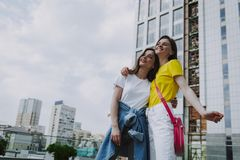 Two happy hipster girls embracing on city view royalty free stock image