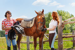 Two happy horseback riders saddling bay horse. Two happy horseback riders, young men and women saddling bay horse standing next to the enclosure fence Royalty Free Stock Photography