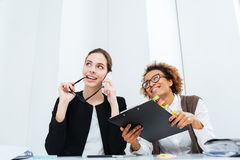 Two happy inspired businesswomen with clipboard dreaming and smiling. Two happy inspired young businesswomen with clipboard dreaming and smiling at workplace Stock Photo