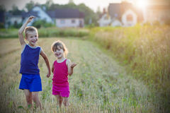 Two happy joyful merry children boy and girl brother and sister. Standing in wheat field with blurred houses on background and having fun. Vintage effect Stock Images
