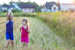 Two happy joyful merry children boy and girl brother and sister. Standing in wheat field with blurred houses on background and having fun Stock Image